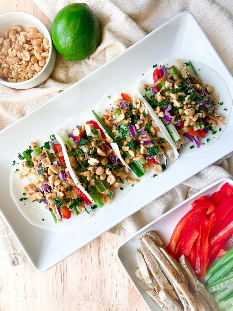 A completed tray of Thai inspired jicama tacos surrounded by extra ingredients.