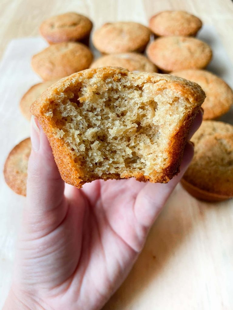 A hand holding a banana muffin with a bite out of it.