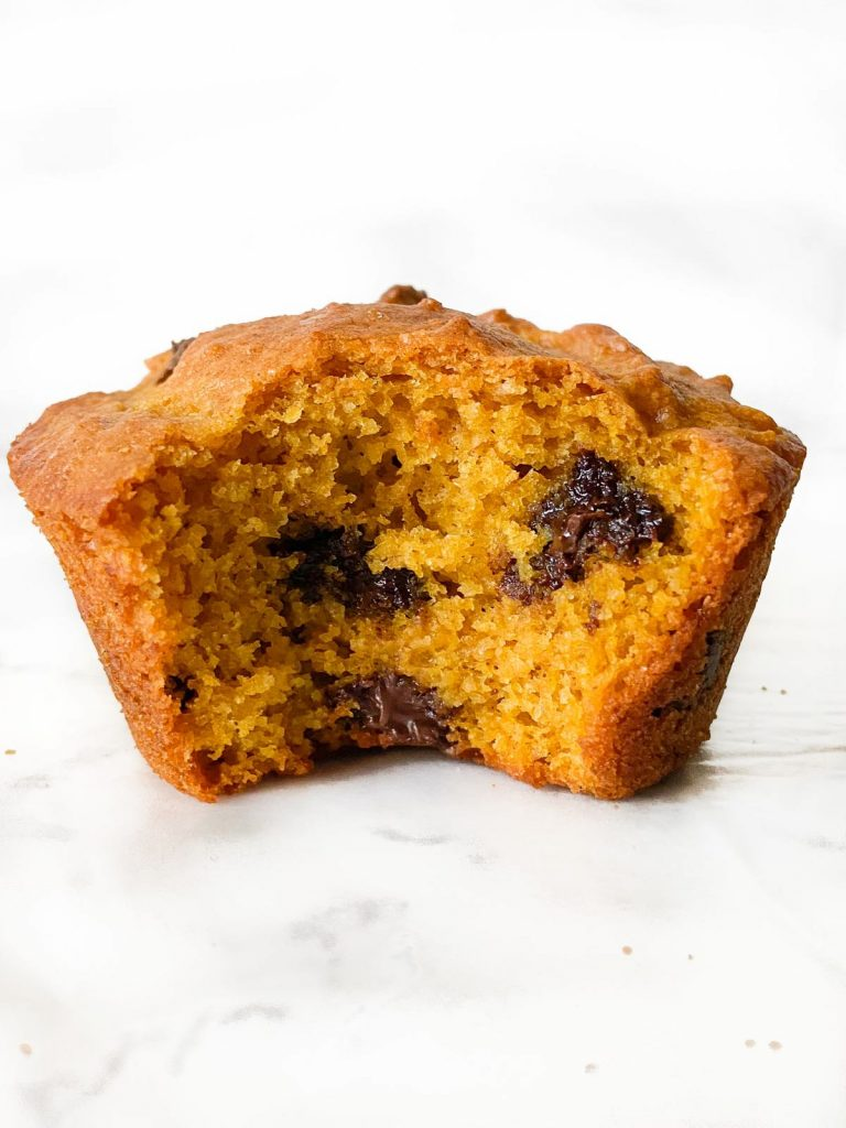 A single pumpkin muffin with a bite out of it.