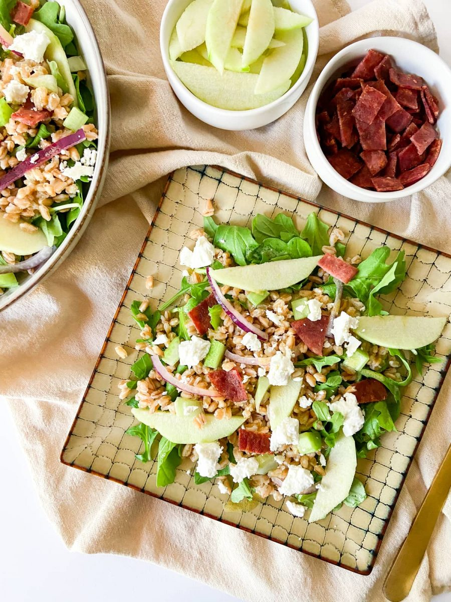 A plate of apple farro and bacon salad with two small bowls filled with extra ingredients.