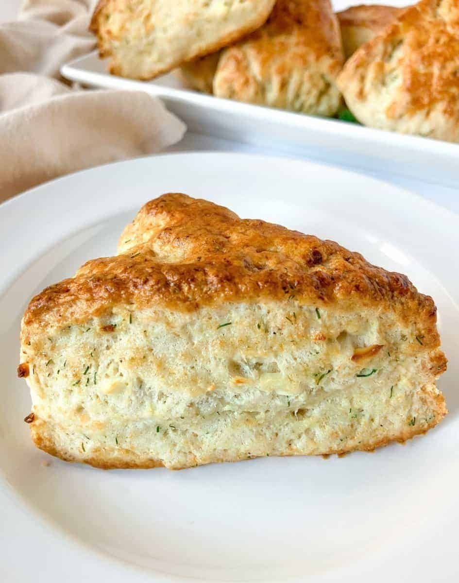 A single dill scone on a white plate.