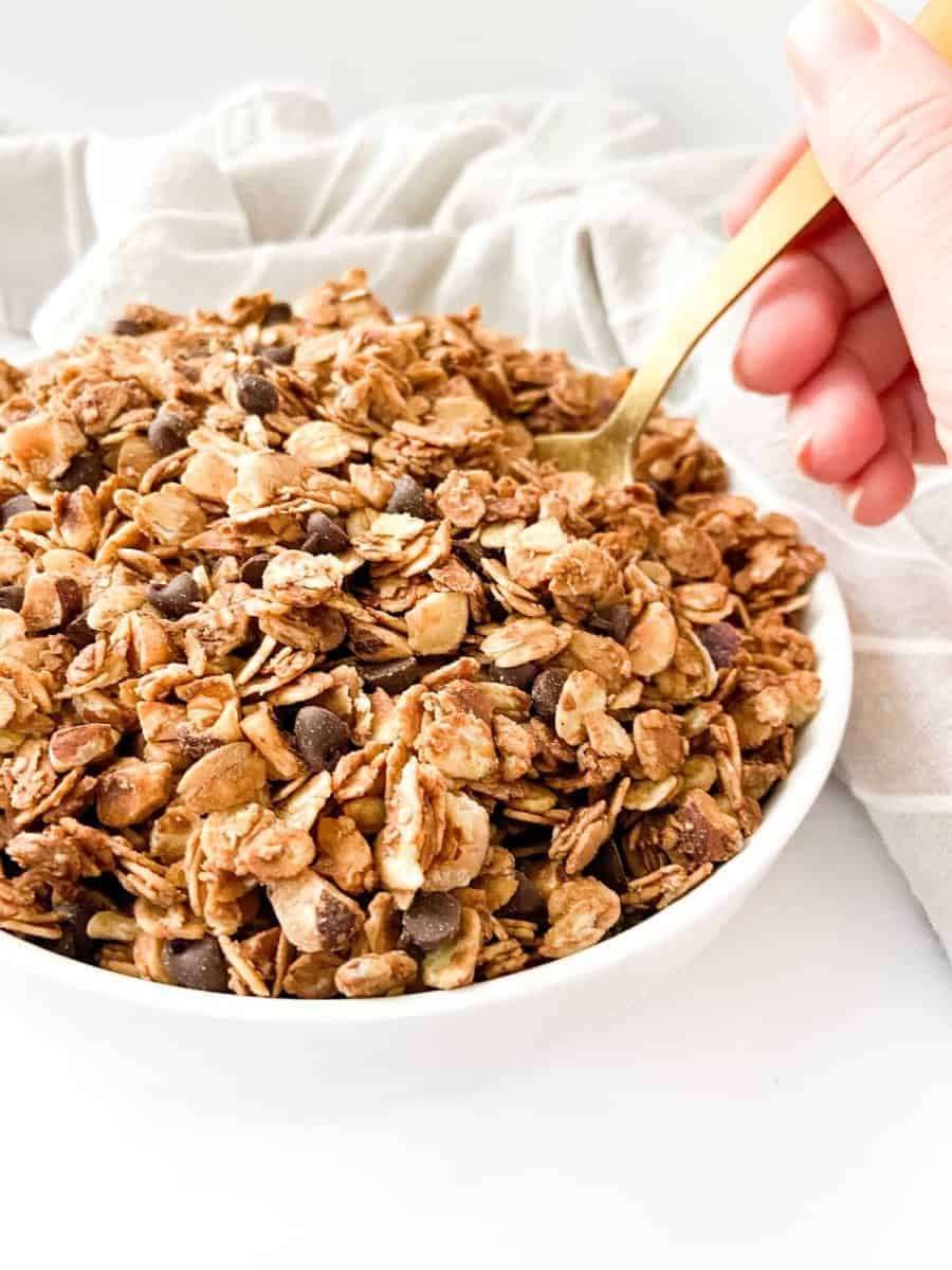 A bowl of chocolate hazelnut granola with a hand scooping into it with a golden spoon.