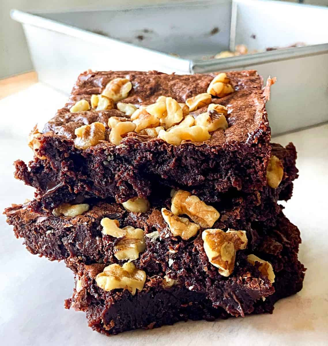 A small stack of brownies with walnuts on top.