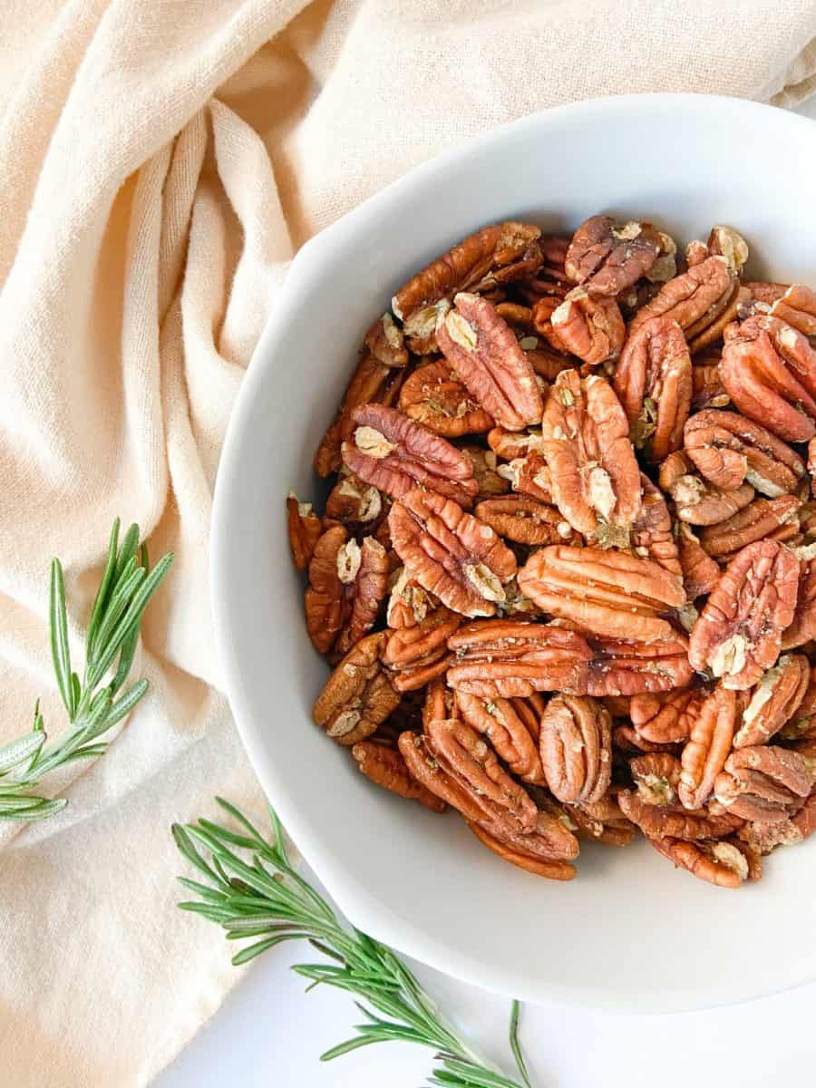 A side shot of a white bowl filled with completed pecans and sprigs of rosemary on the side.