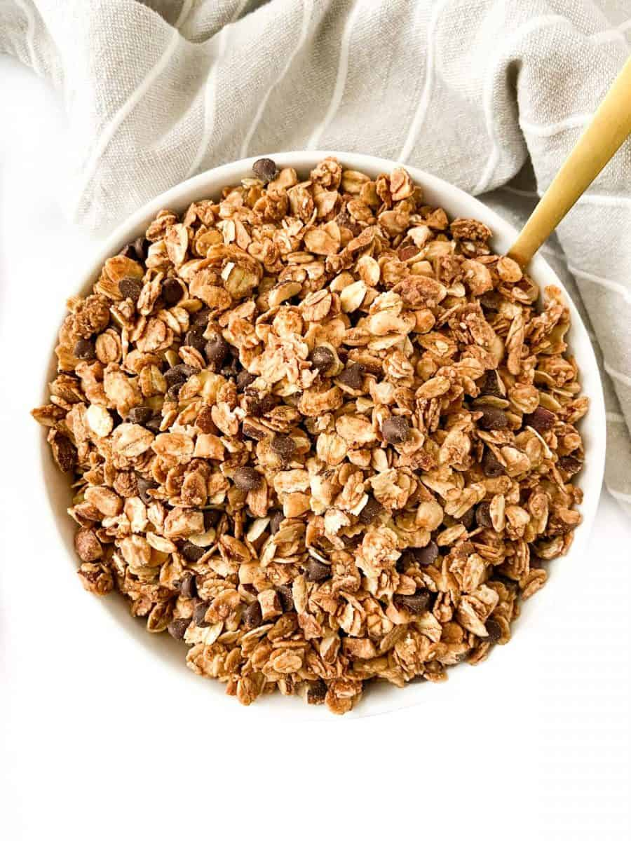 A bowl of chocolate hazelnut granola with a golden spoon.