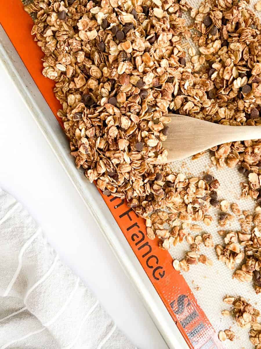 A tray of granola with a wooden spoon.