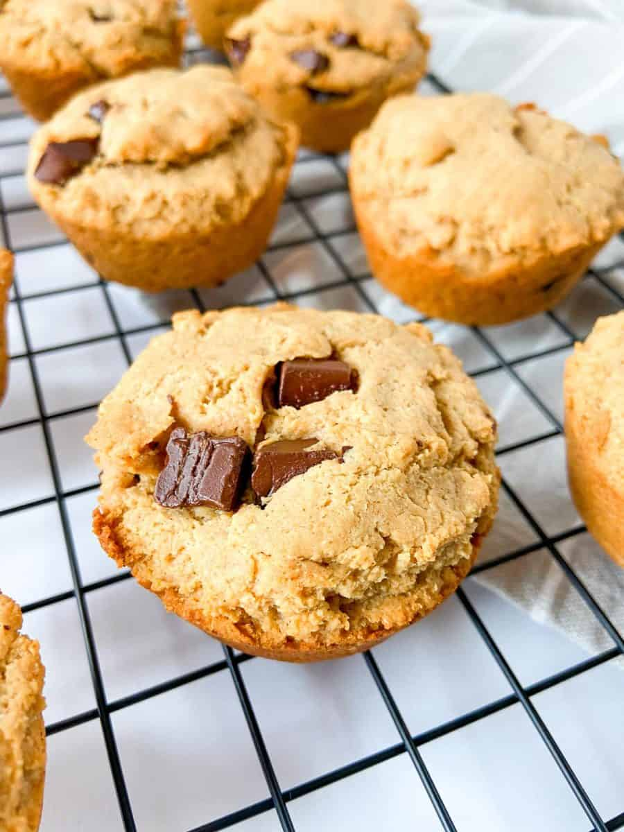 A cooling rack covered in peanut butter protein muffins.
