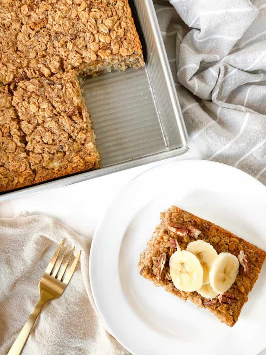 A tray of baked oatmeal and a single slice topped with banana slices on a white plate.