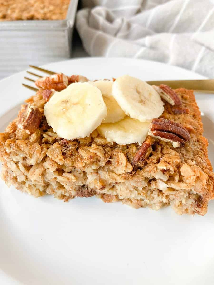 A single banana bread baked oatmeal slice on a white plate with a fork.