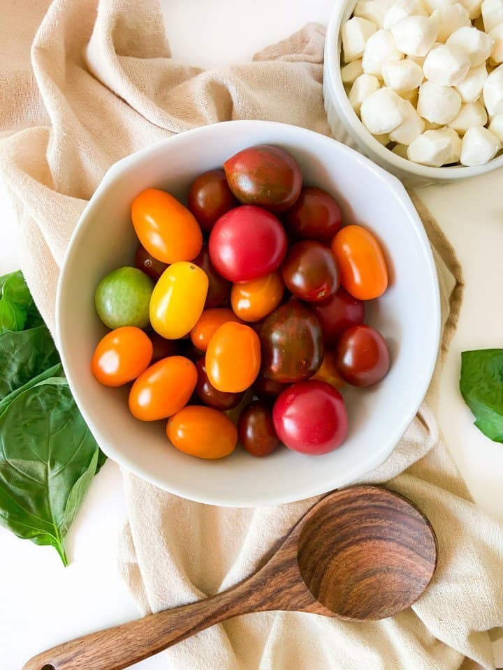Ingredients in Caprese salad: heirloom cherry tomatoes, basil and mozzarella pearls