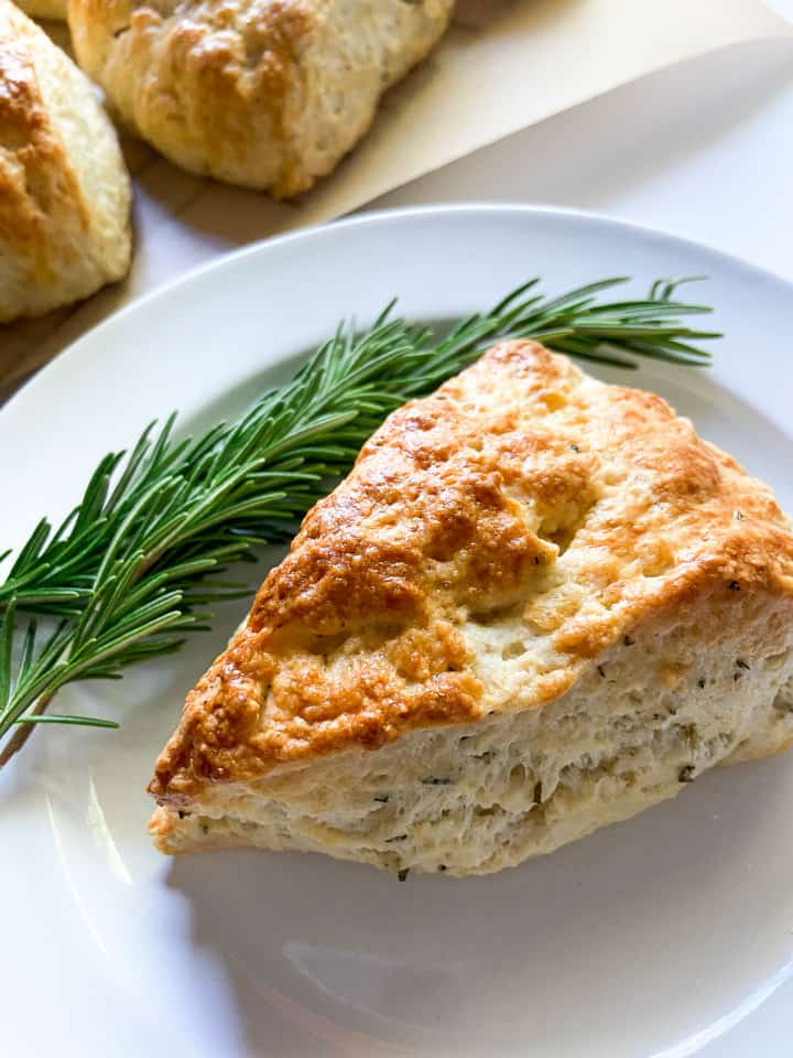a single savory lemon rosemary scone on a plate with fresh sprigs of rosemary