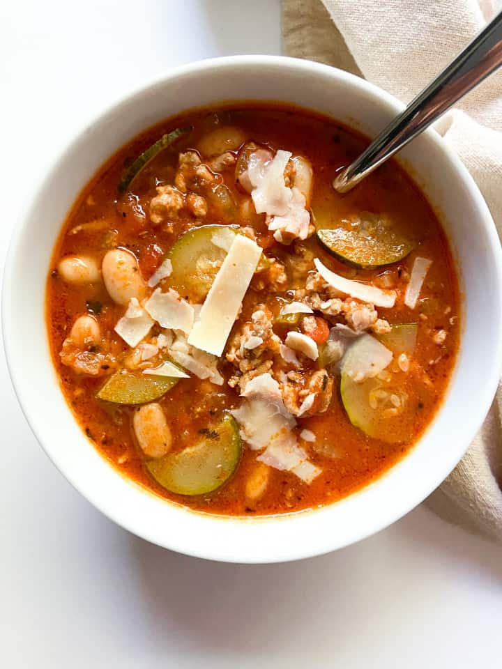 A single bowl of ground turkey soup garnished with Parmesan cheese.