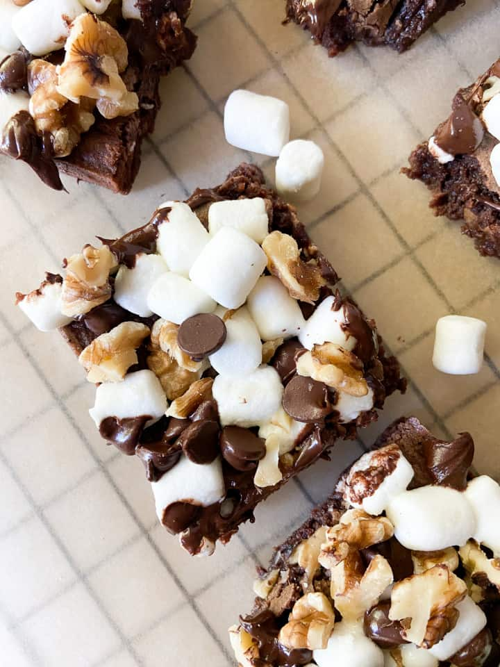 A single rocky road brownie surrounded by marshmallows and other brownie slices.