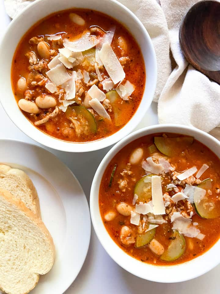 Two bowls of Italian ground turkey soup with a side of bread.