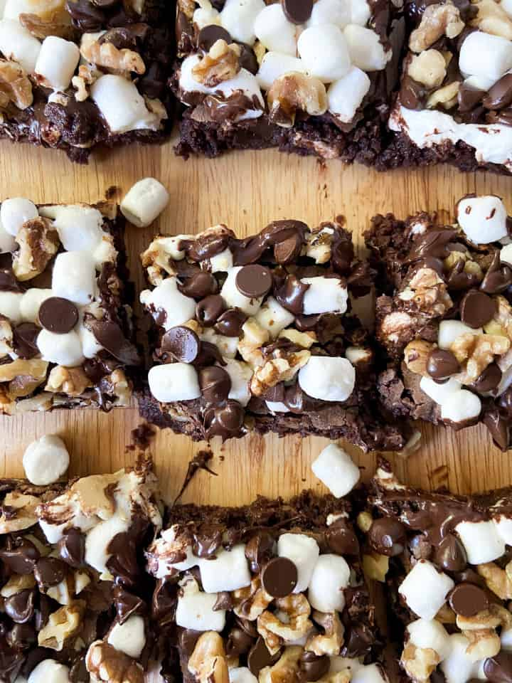 A cutting board covered in warm rocky road brownie slices.