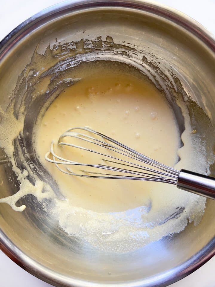A bowl with whisked egg yolks and sugar.