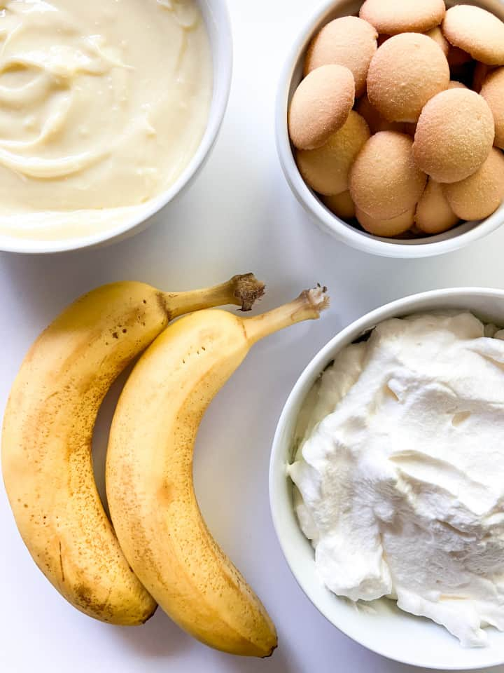A bowl of pastry cream, a bowl of whipped cream, a bowl of mini vanilla wafer cookies, and two ripe bananas.