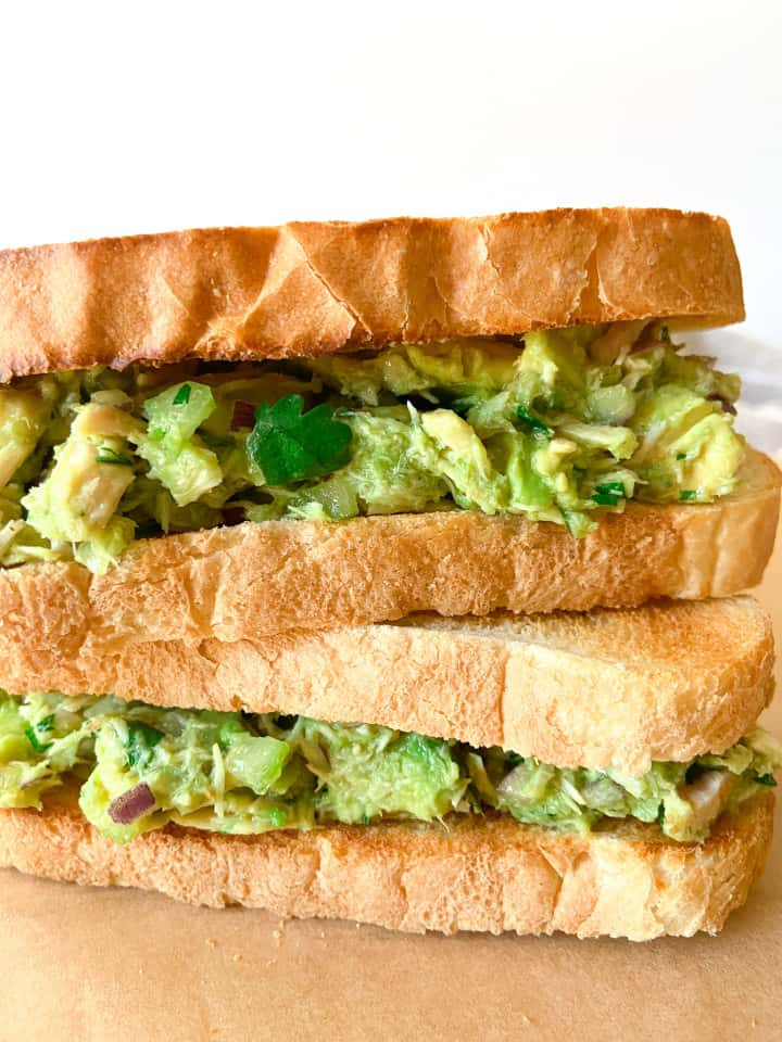 Two completed avocado tuna salad sandwiches on toasted bread.