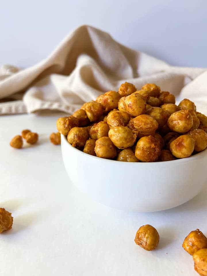 A small white bowl overflowing with crispy chickpeas.