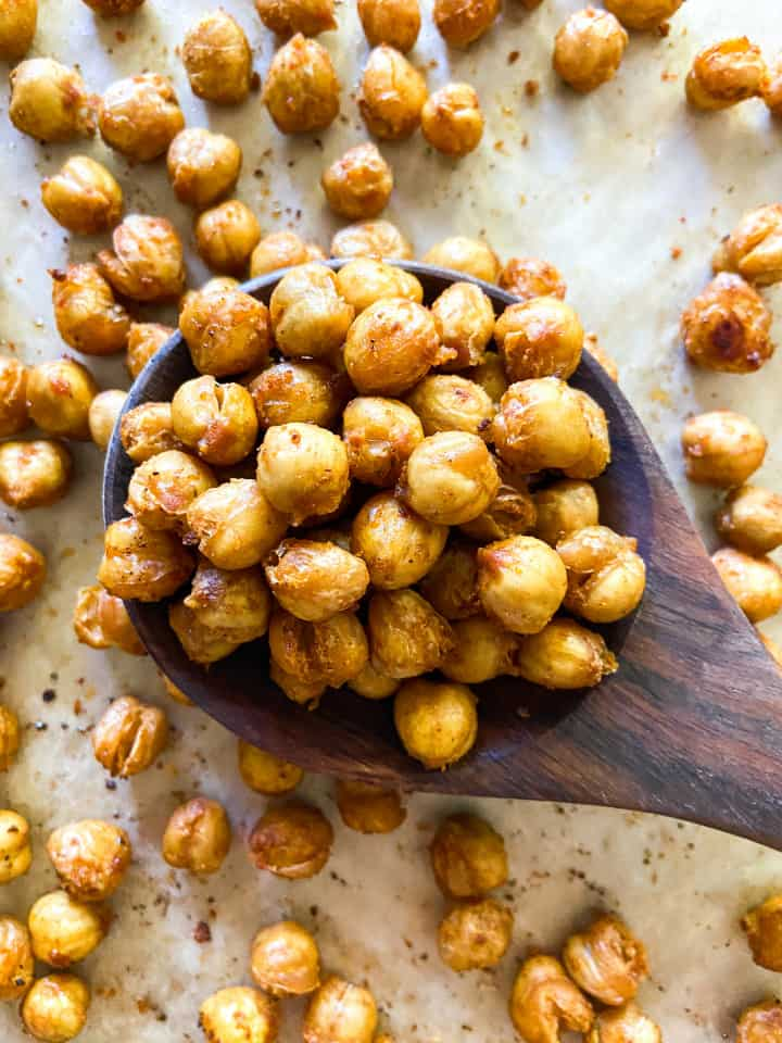 A completed tray of crispy chickpeas, with a wooden spoon full of them.