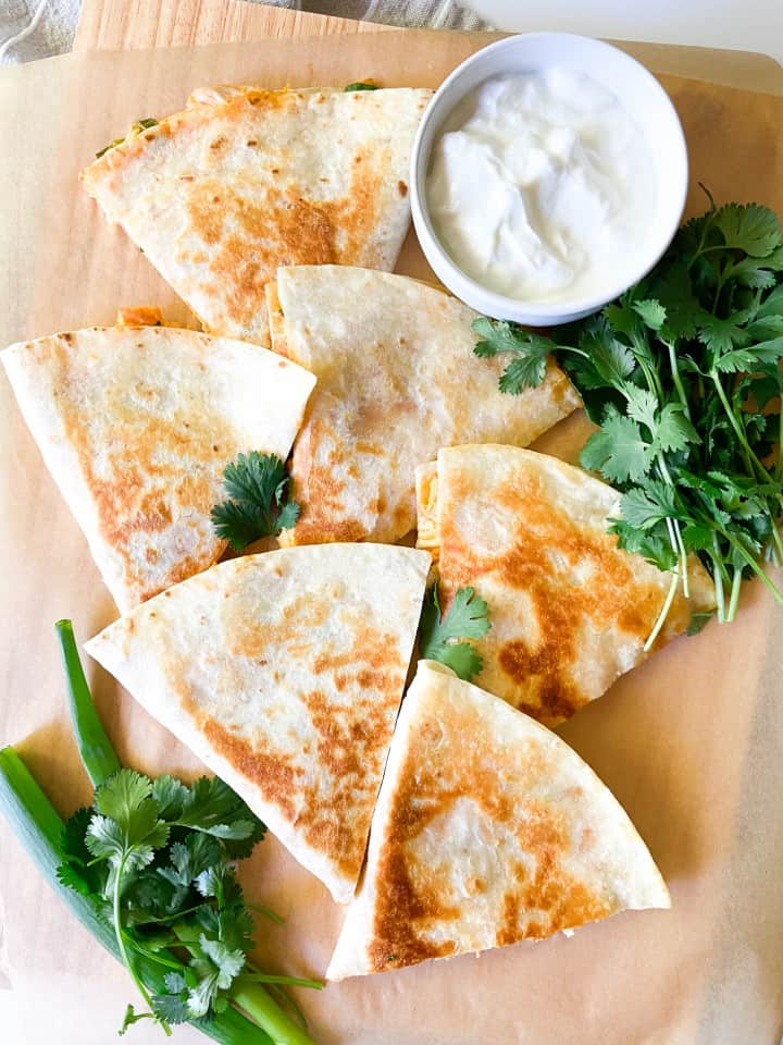 A selection of quesadilla slices spread on to a parchment lined board with sour cream and fresh cilantro.