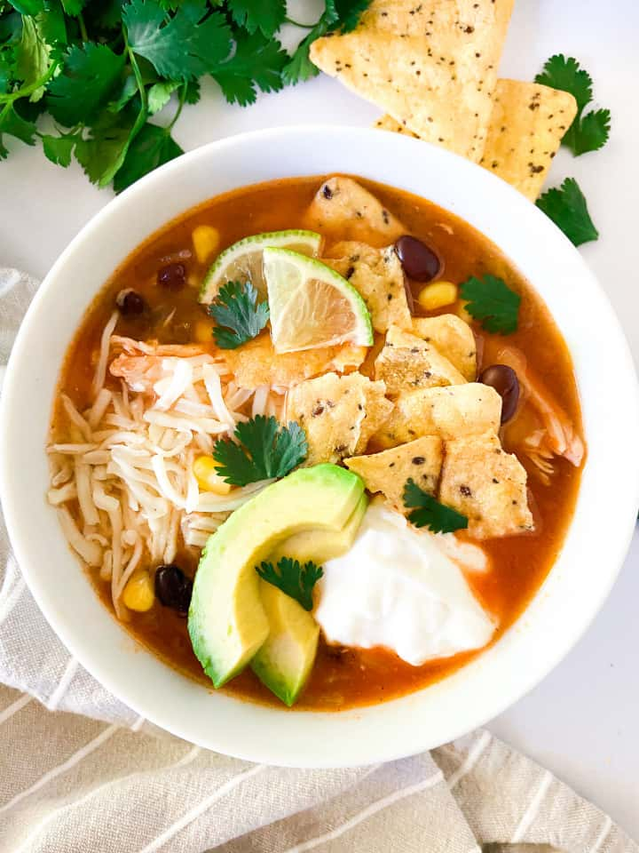 A bowl of soup topped with sour cream, cheese, avocado slices, lime wedges, and cilantro.