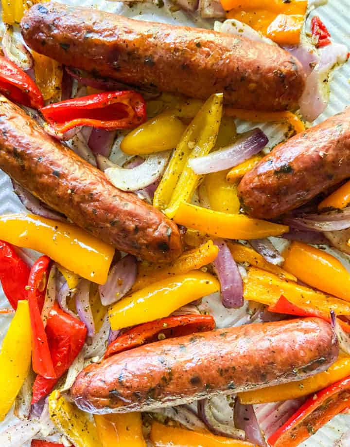Cooked sausage, onions, and peppers on a sheet pan.