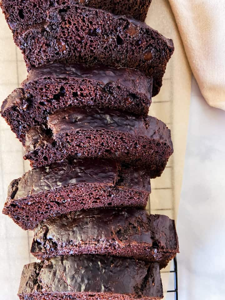 A selection of chocolate zucchini bread slices on a parchment lined cooling rack.