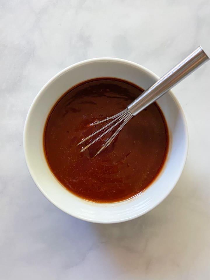 A white bowl full of BBQ sauce.