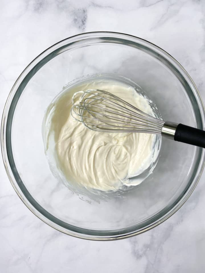 A clear bowl with a whisk and the yogurt dressing.