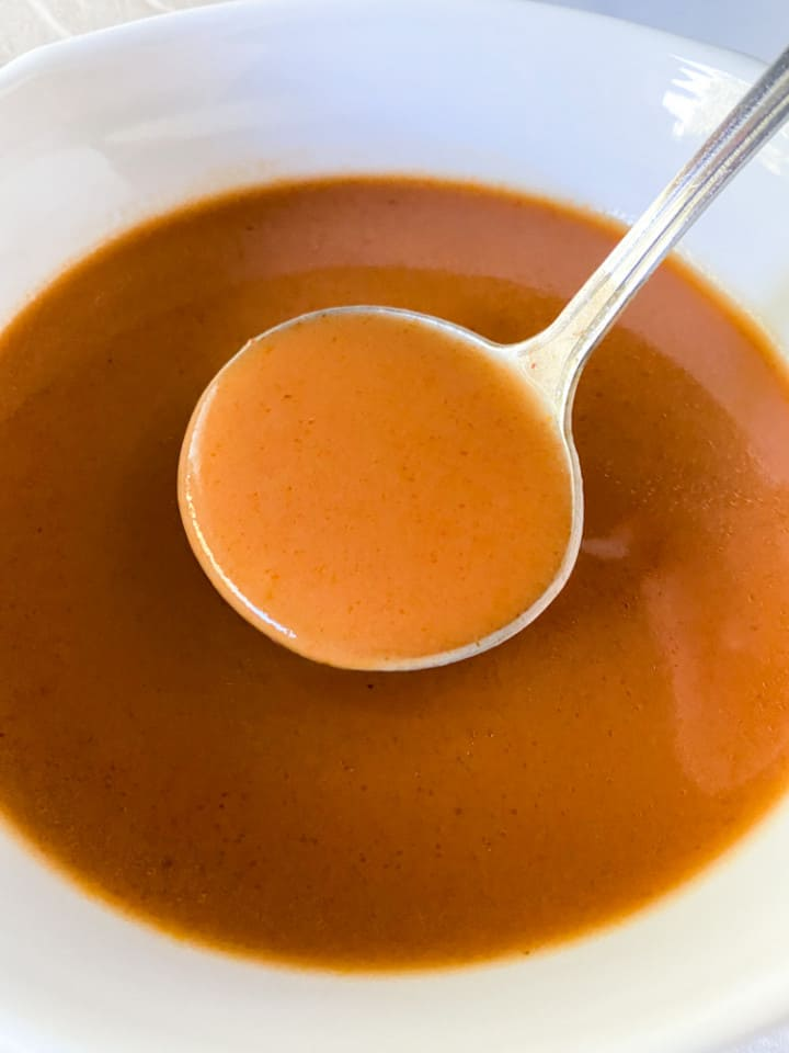 Espagnole sauce in a white bowl with a ladle.