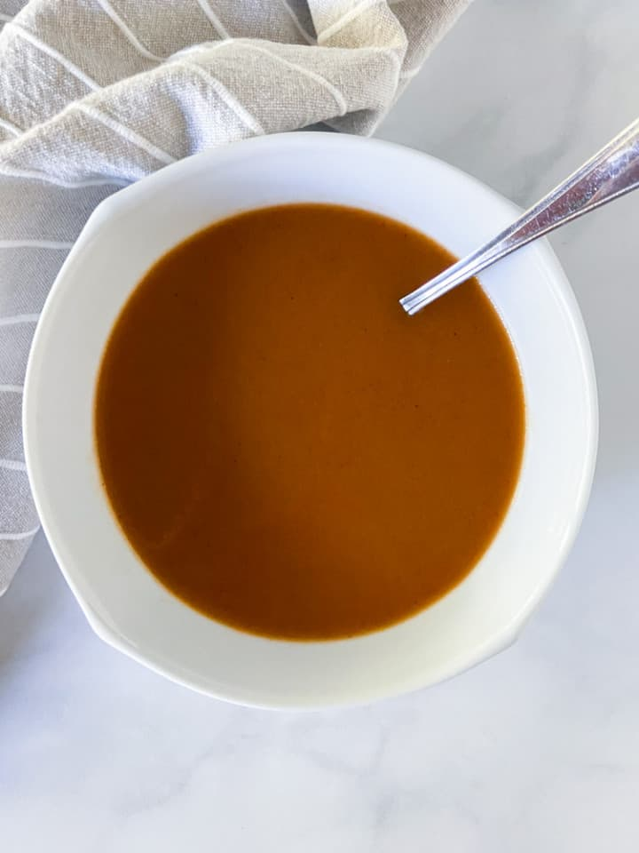 A white bowl filled with sauce and a ladle.