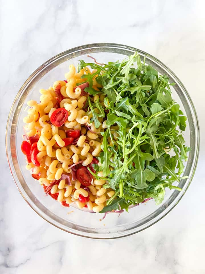 BLT pasta salad with arugula added in a clear bowl.